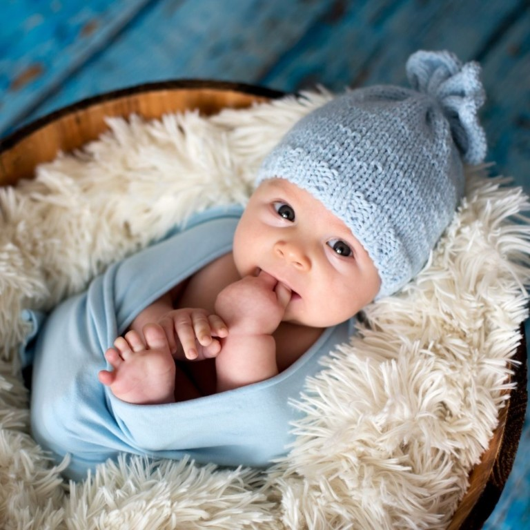 Baby boy in blue crochet hat and blanket